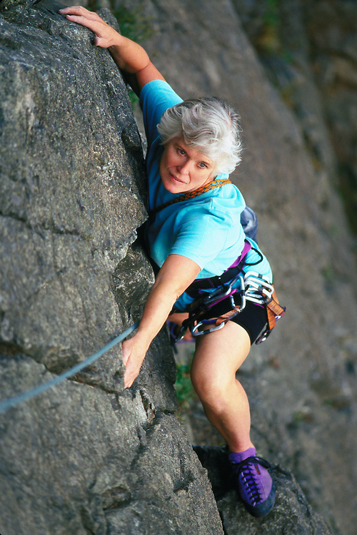 Mature woman rock climbing, using safety rope, elevated view