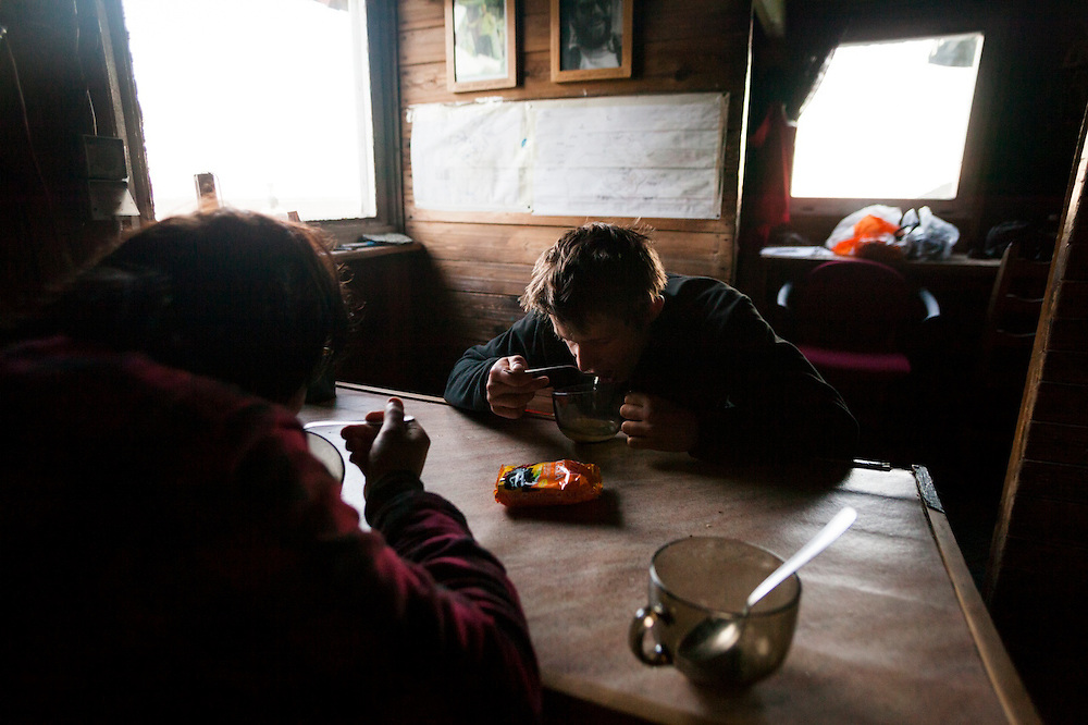 Jaroslaw Halat (right) and Marcin Tukalski, students from the University of Silesia, scarf down ramen noodles after an afternoon in the field at the Polish research station of Baranowka, Svalbard.