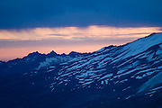 Rain falls on the lower flanks of Mount Baker, in Washington, as the sunset illuminates the fog in the valley below.