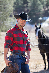hot cowboy with a saddle by a horse on a ranch