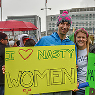 """A young man at the pre-march rally holds a sign reading, """"I love (heart) nasty women."""""""