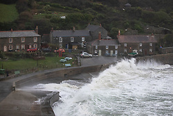 © Licensed to London News Pictures. 18/12/2020. St Austell, UK. Large waves crash onto the road near houses at Portholland cove, Cornwall, during a storm. The south-west is experiencing strong winds of up to 60mph, and and heavy rain with flood warnings. Photo credit : Tom Nicholson/LNP