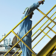 side view of shipyard worker on yellow ladder in Dubai