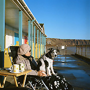A woman and her dog sit outside Bakers Chalets (beach huts), Filey, North Yorkshire, UK