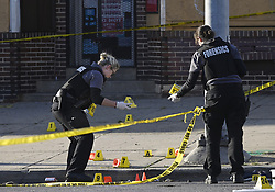 April 28, 2019 - MD, USA - Baltimore police forensics officers place evidence markers next to bullet casings while investigating the scene of a mass shooting at Edmondson and Whitmore avenues, where one man is dead at the scene and seven others were injured. The police are looking for one male shooter who fired into a crowd at a couple of cookouts in the block, according to police commissioner Michael Harrison. (Credit Image: © TNS via ZUMA Wire)