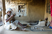 Indian man drinking buttermilk at home in Narlai village in Rajasthan, Northern India