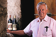Napa Valley, California. Joe Heitz, founder of Heitz Cellars in 1961.  Two of their most well known wines are vineyard designated Cabernet Sauvignons from Martha's Vineyard and Bella Oaks Vineyards. Photographed with a bottle of Cabernet and Chardonnay wine. Photographed in 1989. MODEL RELEASED.