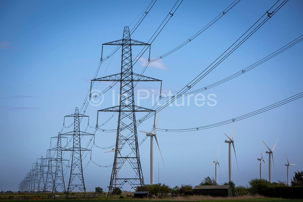 Electrical pylons running alongside wind turbines fromvthe Little Cheyne Court Wind Farm on Romney Marsh, Kent, United Kingdom. The wind farm has a nameplate capacity of 59.8 MW.