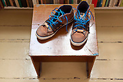 shoe sneakers with bright blue shoelaces standing on a little stool platform