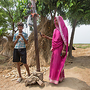 CAPTION: Locals come to charge their cell phones, which they've hooked up to a solar panel designed to power a street light in their village. LOCATION: Singhilpur, Saran District, Bihar, India. INDIVIDUAL(S) PHOTOGRAPHED: Pavan Kumar and Phoola Devi.