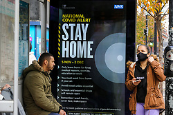 © Licensed to London News Pictures. 10/11/2020. London, UK. People waiting at a bus stop next to the Government's  'STAY HOME' campaign poster in north London as the national lockdown continues. The lockdown in England until Wednesday 2 December, is in place to control the spread of COVID-19 cases. Photo credit: Dinendra Haria/LNP