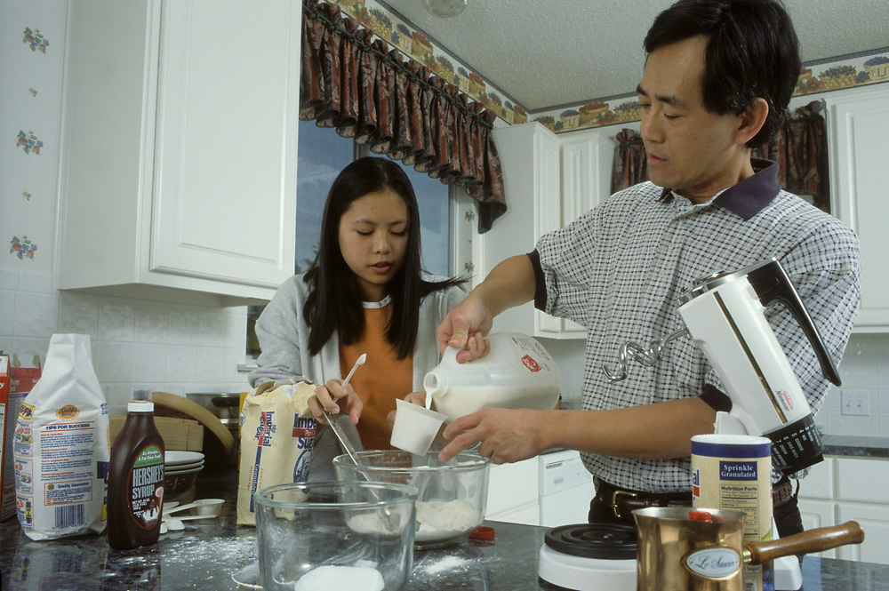 Asian-American (Chinese) father & daughter in kitchen at home. Model Released ©Bob Daemmrich<br /> ©Bob Daemmrich