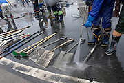 Peace boat volunteers wash dirt off shovels and spades after taking part in the clean-up operations in Ishinomaki, Miyagi Friday May 6th 2011. Around 350 volunteers took part in the relief effort over the Golden Week holiday, including 41 foreigners, clearing mud and removing debris from this coastal town which more almost levelled in the March 11th earthquake and tsunami.
