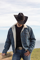 cowboy by a fence on a ranch