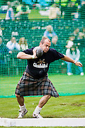 Man competes in shot put contest at the Braemar Games Highland Gathering, Scotland, UK