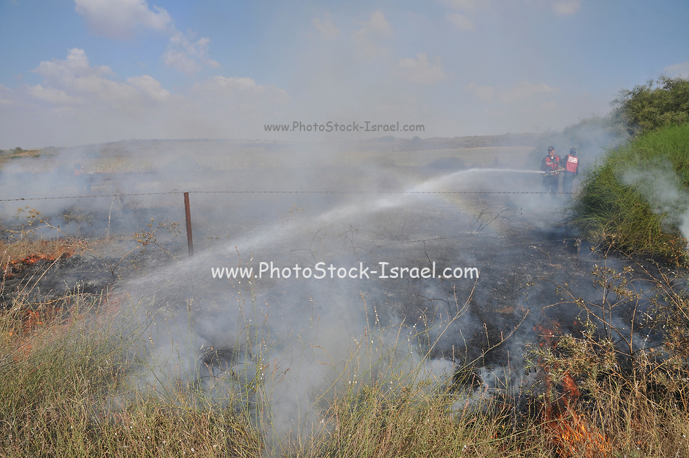 Firefighters fight a fire caused by Palestinian Kite bombs that were flown from Gaza with a lit petrol soaked cloth, to set fires to Israeli fields and crops. Photographed on July 13, 2018 on the Israel Palestine (Gaza) Border
