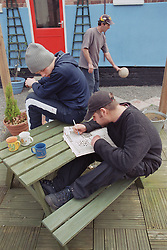 Group of male residents in back garden of Young Persons' Resettlement hostel playing with football and doing newspaper crossword,