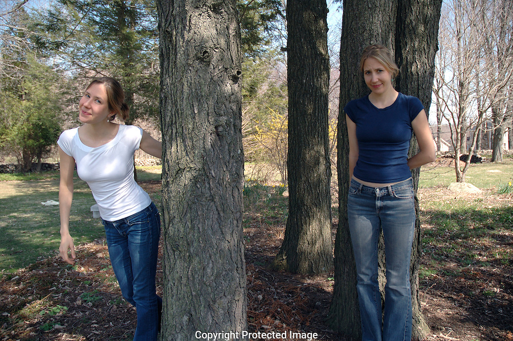 Twin sisters in their mid twenties photographed outside in countryside.