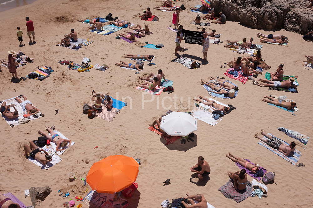 An aerial view of sunbathing individuals, couples and families, on a sandy beach cove, on 12th July 2016, at Cascais, near Lisbon, Portugal. A couple of parasols shade some, and others are topless but otherwise the crowd enjoy the fierce, mid-day heat and sunlight at this seaside resort, a short train ride west from the Portuguese capital. Cascais is a coastal town and a municipality in Portugal, 30 kilometres 19 miles west of Lisbon. The former fishing village gained fame as a resort for Portugals royal family in the late 19th century and early 20th century. Nowadays, it is a popular vacation spot for both Portuguese and foreign tourists and located on the Estoril Coast also known as the Portuguese Riviera.