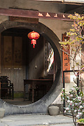 House exterior with round door and tables inside, Xidi village, UNESCO World heritage, Anhui province, China