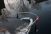 A moored narrow boat lies partially submerged with Christmas tinsel still attached to the bow rail, on 2nd January 2017, in Regent's Canal, central London, England.