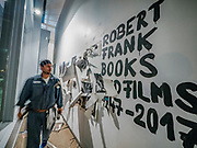 """Portland, Oregon, USA. 26 FEB, 2018. Gallery goers view the photographer Robert Frank's work printed on newsprint in the front window of Blue Sky Gallery in Portland, Oregon, USA. The work was destroyed in a """"Destruction Dance"""" performance defacing the photographs with ink and mutilation with scissors, knives and even ice skates  at the end of it's run. The destruction was Frank's protest regarding today's greed in the global art market."""