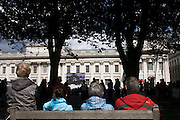 Watching live TV coverage of Equestrian events, spectators and other sports fans sit in summer deckchairs at the old Royal Naval College, Greenwich on day 4 of the London 2012 Olympic Games. Greenwich Park is hosting the Olympic Equestrian competitions, plus the combined running and shooting event of the Modern Pentathlon. The Old Royal Naval College is the architectural centrepiece of Maritime Greenwich, a World Heritage Site in Greenwich, London. The buildings were originally constructed to serve as the Royal Hospital for Seamen at Greenwich, now generally known as Greenwich Hospital, which was designed by Christopher Wren, and built between 1696 and 1712.