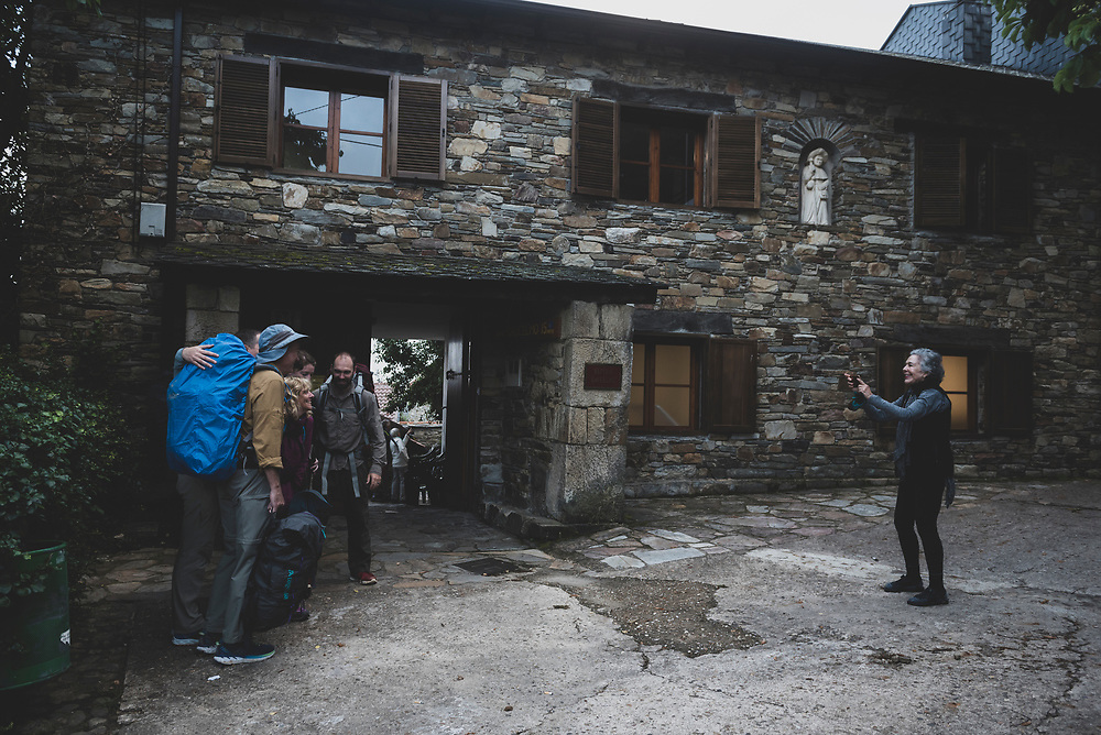Mila Caceres, an American volunter at Refugio Gaucelmo, takes a picture of a group of American pilgrims as they depart for another day on the Camino at 7:30 am. Refugio Gaucelmo is in Rabanal del Camino, one of the higher elevation points on the Camino. (July 1, 2018)