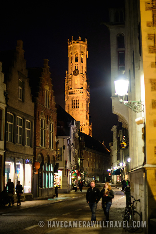 A night scene of one of the streets of the historic old city area of Bruges, Belgium. The illuminated Belfry in the background is one of the city's most recognizable landmarks. The Belfry (or Belfort) is a medieval bell tower standing above the Markt in the historic center of Bruges. The first stage was built in 1240, with further stages on top built in the late 15th century.