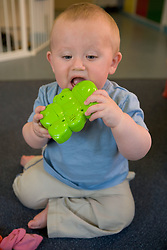 Baby at Nursery School; chewing on a plastic toy,
