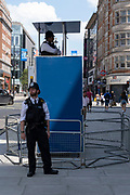 As some non-essential shops re-open, shoppers return to Oxford Street while social distancing measures are put in place by the various retail shops which are open, policemen keep an eye from their podiums on 26th June 2020 in London, England, United Kingdom. As the July deadline approaces and government will relax its lockdown rules further, the West End remains quiet, apart from this popular shopping district, which itself has far fewer people on its pavements than normal.