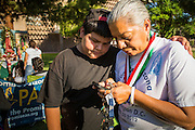 21 JUNE 2012 - PHOENIX, AZ:  LUIS GARCIA (left) comforts PETRA FALCONE while she checks her smart phone for word on the Supreme Court's US v. Arizona decision Thursday. About 40 people, members of the immigrant rights' group Promise AZ (PAZ), gathered at the Arizona State Capitol in Phoenix to wait for the US Supreme Court decision on SB 1070, Arizona's controversial anti-immigrant law, in the case US v. Arizona. The court's ruling is expected sometime later this month. Members of PAZ said they would continue their vigil until the ruling was issued.        PHOTO BY JACK KURTZ