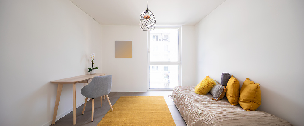 Nice bedroom with a desk, chair and bed. A lot of light enters through the window. Front view