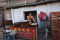 Street food vendor preparing his noodles for the after work rush in a alley, Wenzhou, China.