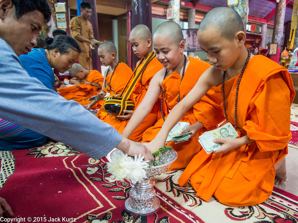 """06 APRIL 2015 - CHIANG MAI, CHIANG MAI, THAILAND:  Family members make merit by presenting alms to boys ordained as Buddhist novices after the boys' ordination on the last day of the three day long Poi Song Long Festival in Chiang Mai. The Poi Sang Long Festival (also called Poy Sang Long) is an ordination ceremony for Tai (also and commonly called Shan, though they prefer Tai) boys in the Shan State of Myanmar (Burma) and in Shan communities in western Thailand. Most Tai boys go into the monastery as novice monks at some point between the ages of seven and fourteen. This year seven boys were ordained at the Poi Sang Long ceremony at Wat Pa Pao in Chiang Mai. Poy Song Long is Tai (Shan) for """"Festival of the Jewel (or Crystal) Sons.  PHOTO BY JACK KURTZ"""