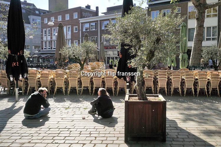 Nederland, Nijmegen, 26-4-2020 Twee jonge mensen zitten op de grond in het stadscentrum op een plek die normaal vol staat met terrasjes .De horeca is al enkele weken gesloten vanwege de coronadreiging en veel ondernemers willen dat de regering het normale dagelijks leven weer langzaam laat opstarten . Unlock,beperkende,opheffen,versoepelen,versoepeling . Foto: Flip Franssen