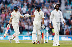 England's Alastair Cook and Joe Root bump fists as they start to walk off at the end of the day's play during the test match at The Kia Oval, London.