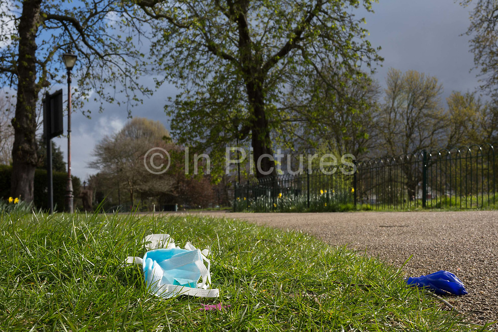 At the beginning of the second week of the UKs Coronavirus lockdown and in accordance with government guidelines for social distancing and local daily exercise, a used discaded surgical mask and glove lies in the grass alongside a path used by passing Londoners in Ruskin Park, a green public space in the borough of Lambeth, south London, on 30th March 2020, in London.