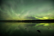 The Aurora reflects on the waters of Bartlett Cove, Alaska