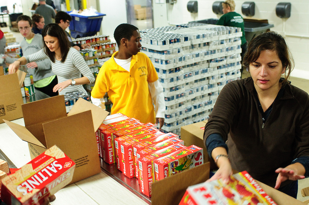 Equip for Equality Staff Attorney Rachel M. Arfa (R) joins fellow members of the Chicago Bar Association's Young Lawyers Section volunteering with several other groups packing canned and dry goods into boxes at the Greater Chicago Food Depository on Wednesday, November 7th. Hundreds of the boxes will be delivered to the City of Chicago Department of Family and Support Services locations. © 2012 Brian J. Morowczynski ViaPhotos