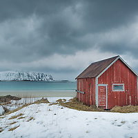 A tiny, weather beaten house adds a bright pop of color to a stormy day along one of Lofoten's beautiful arctic beaches.