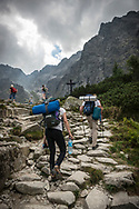 Two people with camping gear and backpacks hike up a rocky trail connecting Morskie Oko to Czarny Staw in Tatra National Park, Poland (August 29, 2016)