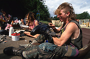 Cleaning boots. Road Protest actions around the M65 extension. This involved protecting and squatting a group of houses, and also squatting treehouses in the forest at  Stanworth Valley Preston Lancashire. 1995<br /><br />The British Road Protesters movement began in the early 1990s when the Donga tribe squatted Twyford Down to save this beautiful site, a site of scientific interest SSI from the Ministry of transport's road building programme which threatened to destroy the landscape. The Dongas was the name of the ancient walkways, the paths trodden in the middle ages by people walking down to Winchester. A small tribe were joined by people of all walks of life who came to Twyford Down to defend it. A long hard battle over several years ended in the 'cutting' a new motorway built through this ancient monument and destroying it. <br /><br />The Road Protest movement in Britain continued for many years and more battles were fought in London against the MII both at Wanstead then in Leytonstone, and subsequently at Newbury, and in Sussex. the protesters were very inventive in their use of non violent peaceful direct action. They barricaded themselves into squats, made tree houses, tunnels and have huge demonstrations against the bailliffs, police and security who tried to force their way through the defences of this alternative environmental popular movement. Many of the roads were built eventually and many sites of great beauty lost, but the government had to stand down from its road building policy and eventually the programme was halted. the protests cost the government billions. Out of that movement grew many environmental NGOs who have to this day kept fighting for ecological and sustainable environmental solutions rather than following the cult of the car, petrol and roadbuilding..