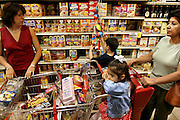 (MODEL RELEASED IMAGE). Trying to contain the children in the giant shopping cart, Diana Fernandez and her mother, Alejandrina Cepeda, prowl the local H-E-B supermarket in San Antonio, Texas. Diana's son Brian, 5, who repeatedly self-ejects from the cart, must be constantly reminded that the impulse items hung in every aisle are not on the shopping list. Hungry Planet: What the World Eats (p. 274).