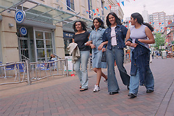 Group of teenage girls in town on shopping trip; walking with linked arms,