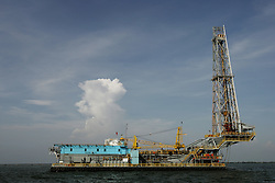 """An offshore oil drilling rig sits on Lake Maracaibo.  Since the removal of nearly 18,000 workers after an oil strike in Venezuela in 2002, PDVSA, the state run oil company has gone through drastic changes.  Struggling to replace the dismissed workers and return production to pre-strike quantities, PDVSA has also undertaken the financing and coordination of huge social programs.  PDVSA has invested billions of dollars in various education, food, medicine and infrastructure projects, calling itself the """"new"""" PDVSA."""