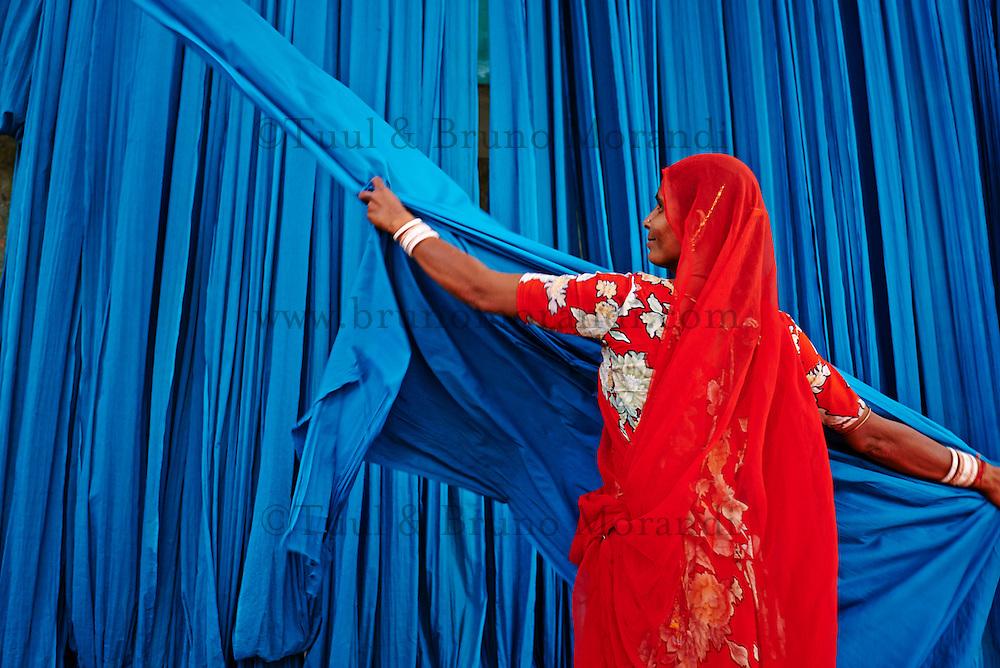 Inde, Rajasthan, Usine de Sari, Puspa, 32 ans. Les tissus sechent en plein air. Ramassage des tissus secs par des femmes et des enfants avant le repassage. Les tissus pendent sur des barres de bambou. Les rouleaux de tissus mesurent environ 800 m de long. . // India, Rajasthan, Sari Factory, Puspa, 32 old. Textile are dried in the open air. Collecting of dry textile  are folded by women and children. The textiles are hung to dry on bamboo rods. The long bands of textiles are about 800 metre in length.