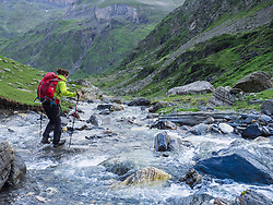 Woman hiking in the High Pyrenees near Cirque de Troumouse, crossing wild river, France
