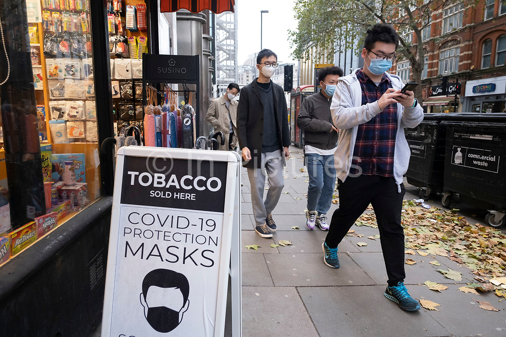 Face masks for sale as Londoners await the imminent second coronavirus lockdown it's business as usual in the West End with large numbers of people, some wearing face masks and some not, on what will be the last weekend before a month-long total lockdown in the UK on 1st November 2020 in London, United Kingdom. The three tier system in the UK has not worked sufficiently, to suppress the virus, and there have have been calls by politicians for a 'circuit breaker' complete lockdown to be announced to help the growing spread of the Covid-19.