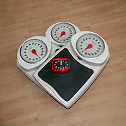 Dieting, weight loss and body image conceptual image of three analogue scales stacked one on top of the other with a clock for urgency